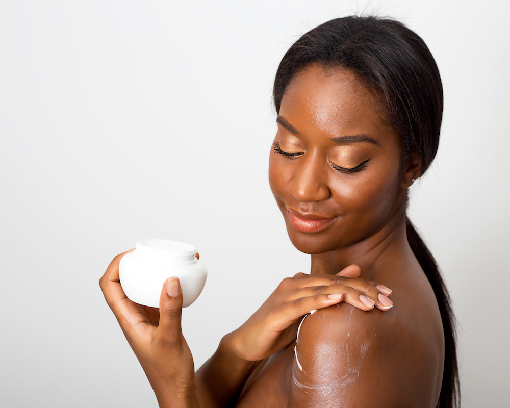 black woman applying moisturizer to skin