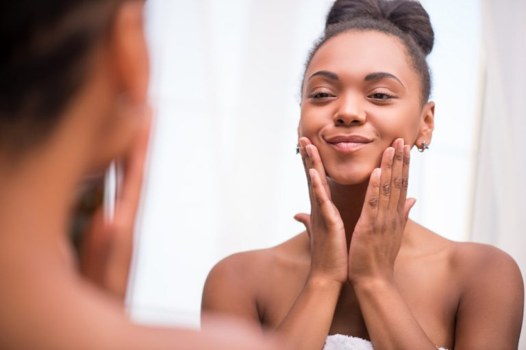Smiling young black woman in a bathroom touching her clean soft face